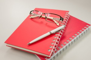 eye glasses with notebook and pen