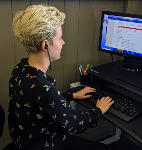 Person wears under the chin headphones as they type on the computer.